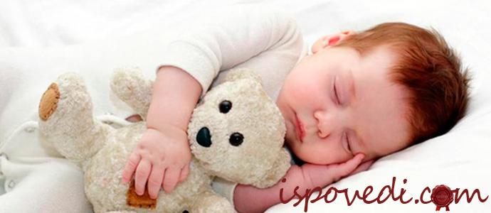 маленький ребенок спит с игрушкой