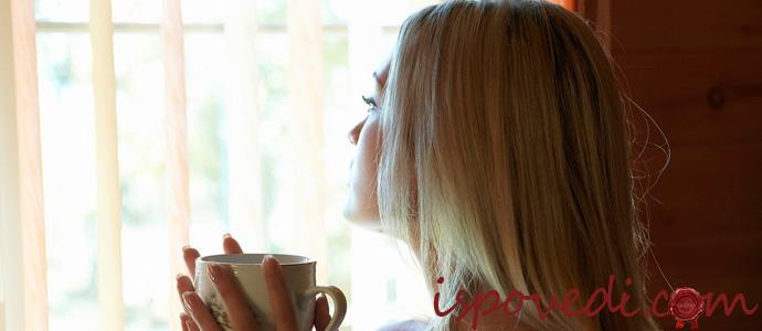 девушка с чашкой кофе размышляет у окна