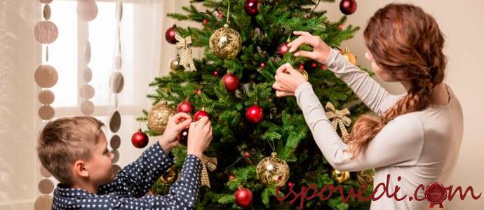 мама и сын наряжают новогоднюю елку