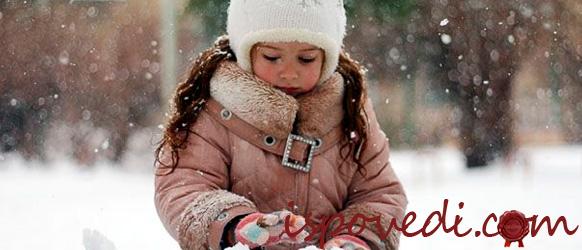 Девочка играет зимой в снегу