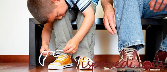 Сын учится завязывать шнурки в новой обуви