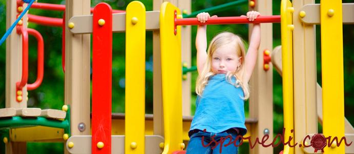 ребенок на спортивном комплексе делает зарядку